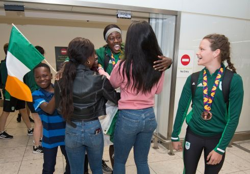 WELCOME: Tallaght AC's Rhasidat Adeleke is greeted by friends and family at Dublin airport this morning after her 100m and 200m sprint Gold medal-winning performances at The European Youth Olympics in Baku. Fellow medallist, swimmer Molly Mayne looks on. Photograph: Dave Meehan