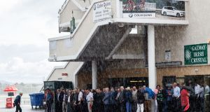 Racegoers shelter during a rain shower at the opening day of the 2019 Galway Festival. Photo: James Crombie/Inpho