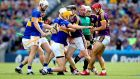 Referee Seán Cleere looks on as Wexford and Tipperary players clash during  the All-Ireland hurling semi-final at Croke Park. Photograph: Ryan Byrne/Inpho