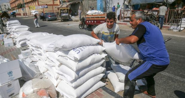 Palestinian men pile bags of flour outside an aid distribution centre run by Unrwa in the central Gaza Strip refugee camp of Bureij, on Wednesday. Photograph: Said Khatib/AFP/Getty Images