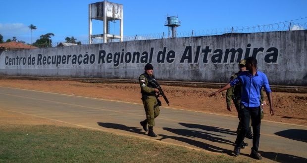 A police officer patrols the perimeter of the Altamira prison in Pará state, where 58 people were killed in a fight between rival gangs.  Photograph:  Bruno Santos/AFP/Getty Images