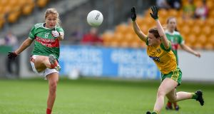 Sarah Rowe kicks a point despite the efforts of Donegal's Niamh Carr during the clash  at Bord Na Mona O'Connor Park in Tullamore, Offaly. Photo by Ben McShane/Sportsfile