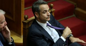 Greek prime minister Kyriakos Mitsotakis adjusts his tie during a parliamentary session  in Athens. Photograph: Costas Baltas/Reuters