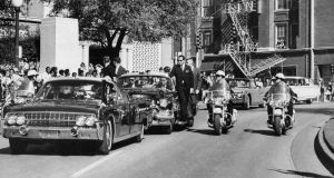 US president John F Kennedy's hand reaches toward his head within seconds of being fatally shot as first lady Jacqueline Kennedy holds his forearm as the motorcade proceeds along Elm Street past the Texas School Book Depository in Dallas in November 1963. Photograph: James  Altgens