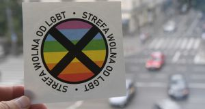 "A picture taken  in Warsaw shows a sticker bearing a large black cross over an LGBT+ rainbow motif and reading ""This is an LGBT-free zone"", that is distributed with the latest issue of magazine Gazeta Polska, a news magazine close to Poland's right-wing government. Photograph: Janek Skarzynski (AFP/Getty Images)"