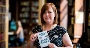 Lyra McKee's sister Nichola Corner holds aloft a copy of her sister's book, Angels With Blue Faces. Photograph: Liam McBurney/PA Wire
