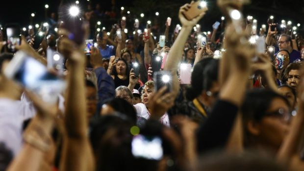 People hold up their phones in lieu of candles at an interfaith vigil for victims of a mass shooting, which left at least 20 people dead, on August 4th, 2019 in El Paso, Texas. Photograph: Mario Tama/Getty Images