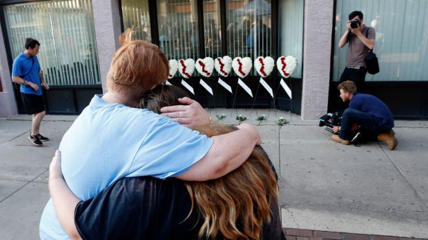 Two women hug each other in front of wreaths displayed for the nine victims of a shooting, in the Oregon District of Dayton, Ohio, August 4th 2019. Photograph: David Kohl/EPA