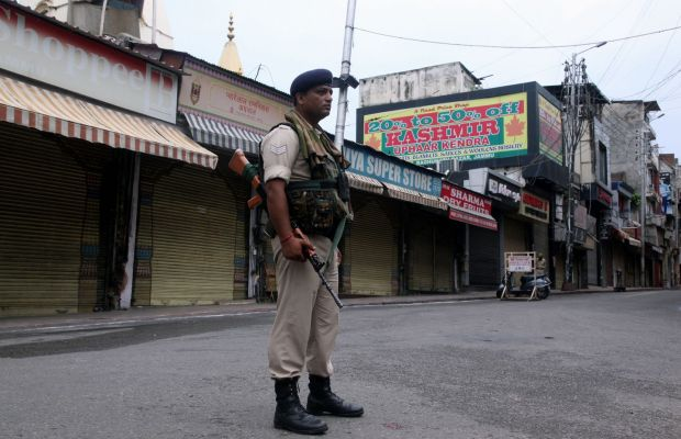 A security personnel stands guard next to closed shops in Jammu on Wednesday. Photograph: Rakesh Bakshi/AFP/Getty Images