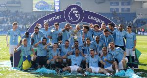 Manchester City players celebrate with the Premier League trophy after winning the title at   Brighton back in May. Photograph:  Mike Hewitt/Getty Images
