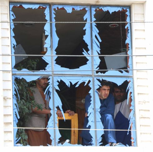 NEAR MISS: People peer through damaged window panes near the scene of a bomb blast in Herat, Afghanistan. At least four people were injured. Photograph: Jalil Rezayee/EPA