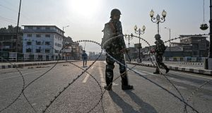 Indian paramilitary troopers stand guard behind a barbed fence wire as they block a road during a curfew in Srinagar on Monday. Photograph: Tauseef Mustafa/AFP/Getty Images