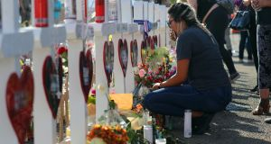 Mayte Santiesteban pays her respects at a makeshift memorial at the Walmart in El Paso, Texas,  after a gunman opened fire inside the store, killing 22 and wounding more than two dozen others. Photograph: Jim Wilson/The New York Times