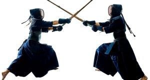 Two Kendo martial arts fighters combat fighting in silhouette isolated on white background