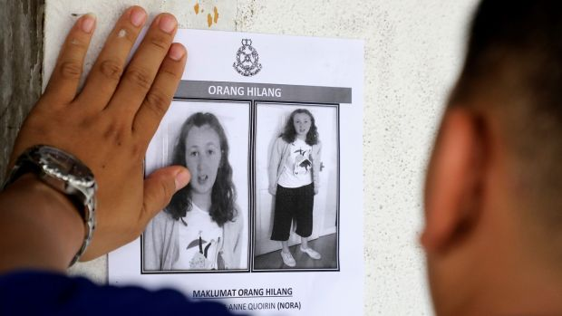 A police officer pastes a photo of missing 15-year-old Irish girl Nora Quoirin on a wall at a shop in Seremban, Malaysia, August 9th, 2019. Photograph: Lim Huey Teng/Reuters