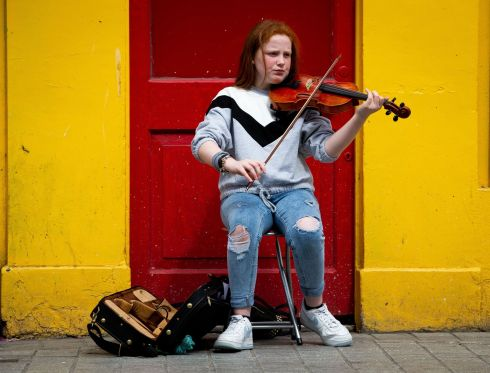 EARNING HER STRIPES: Ella Rooney (12),  from Drogheda, busks on the street during this year's Fleadh Cheoil na hÉireann, in Drogheda, Co Louth. Photograph: Tom Honan