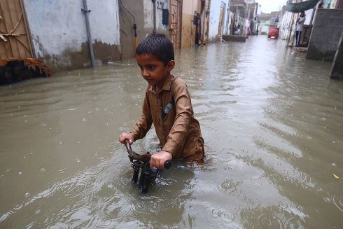 NO STOPPING HIM: A boy plays in flash floodwater after monsoonal rains in Karachi, Pakistan. At least 12 people were electrocuted fatally during the storm. Photograph: Shahzaib Akber/EPA