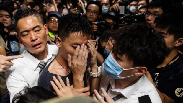 A man alleged to be a mainland police officer is surrounded by security officials and protesters at the Hong Kong International Airport in Hong Kong, China. Photograph: Kyle Lam/Bloomberg