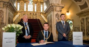 Belfast lord mayor John Finucane, centre, with Belfast high sheriff Tommy Sandford, left, and deputy lord mayor Peter McReynolds during the signing of the book of condolence at Belfast City Hall. Photograph: Liam McBurney/PA Wire