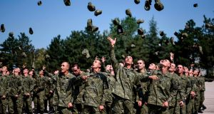 New recruits of the Kosovo Security Force throw their caps in the air during their swearing-in ceremony at the Adem Jashari barracks in Pristina. Photograph: Armend Nimani / AFP