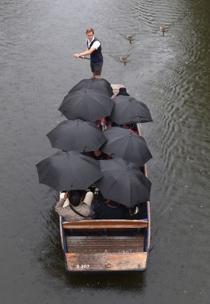 COVERING UP: People shelter under umbrellas as they punt along the River Cam in Cambridge, as heavy rain and thunderstorms hit parts of Britain on Wednesday. Photograph: Joe Giddens/PA Wire