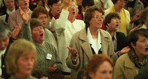 The photograph appeared in The Irish Times on the 18 November 1996 page 4. The caption read: Delegates singing at the Silver Jubilee Charismatic Renewal Conference at the RDS, at the weekend. Photograph: Paddy Whelan