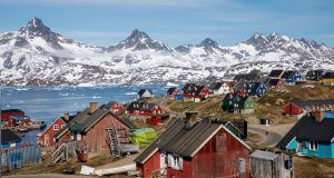 Snow covered mountains rise above the harbour and town of Tasiilaq, Greenland. Photograph: Lucas Jackson/Reuters