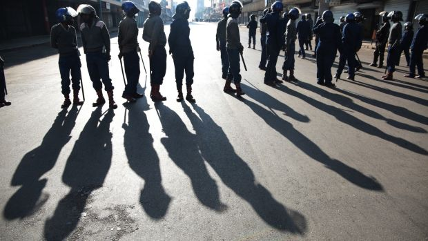 Members of the Zimbabwe Republic Police block the road to contain the planned Movement For Democratic Change Alliance Peace March in Harare. Photograph: Aaron Ufumeli/EPA