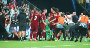 Liverpool's goalkeeper Adrián being helped by teammates after a pitch invader rushed into him in Istanbul. Photograph: Tolga Bozoglu/EPA