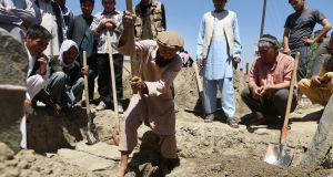 Men dig graves for three bomb blast victims, all members of one family,  a day after a suicide attack targeted a wedding hall in Kabul, Afghanistan. Photograph: Jawad Jalali/EPA