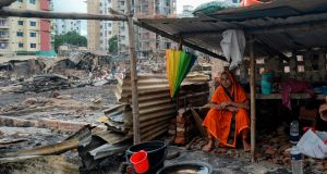 A resident rests in a temporary shelter in a slum in Dhaka on Sunday, after a fire broke out late on Friday in Mirpur town. There were no fatalities. Photograph: Munir Uz Zaman/AFP/Getty Images