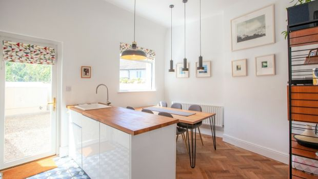 The eat-in kitchen has smart white Ikea units and timber countertops with a neat island dividing the dining table from the worktops