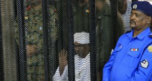 Sudan's deposed military ruler Omar al-Bashir sits in a defendant's cage during the opening of his corruption trial in Khartoum on Monday. Photograph: Ebrahim Hamid/AFP/Getty Images