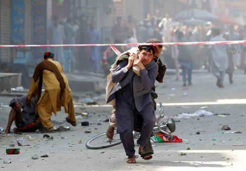 AFGHAN BOMBING: A man carries a wounded person to the hospital after a blast in Jalalabad, Afghanistan. Photograph: Parwiz/Reuters