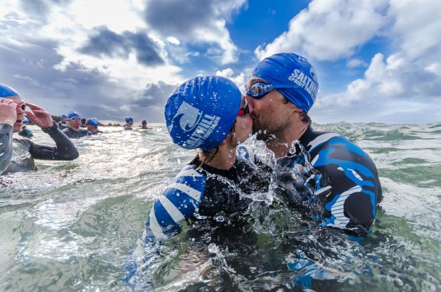 Two swimmers kissing before heading out to open water during the triathlon in Salthill in Galway. Photograph: Martin Kalvaster