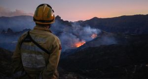 A firefighter observes flames rising from a forest fire near the village of Ayacata in Tejeda on the island of Gran Canaria on Tuesday. Photograph: Getty Images