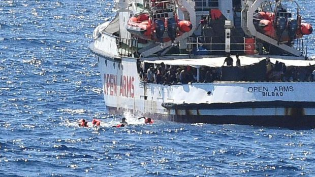 Migrants swim after jumping off the Spanish rescue ship Open Arms. Photograph: Guglielmo Mangiapane/Reuters
