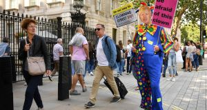 A demonstrator, dressed as a clown and wearing a mask of Britain's Prime Minister Boris Johnson, protests outside the gates to Downing Street