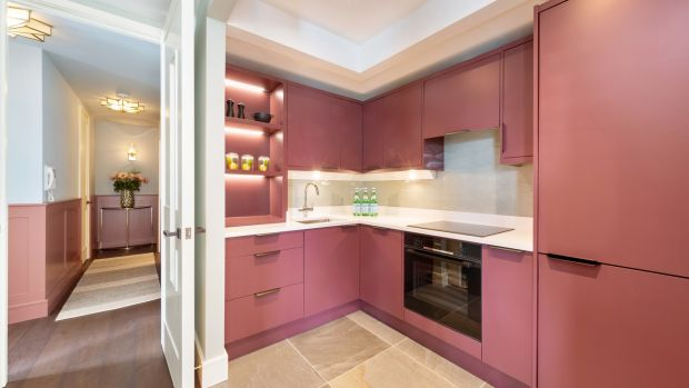 A kitchen wall was removed and the units are painted in Adventurer by Little Greene. Photograph: Matteo Tuniz MediaPro