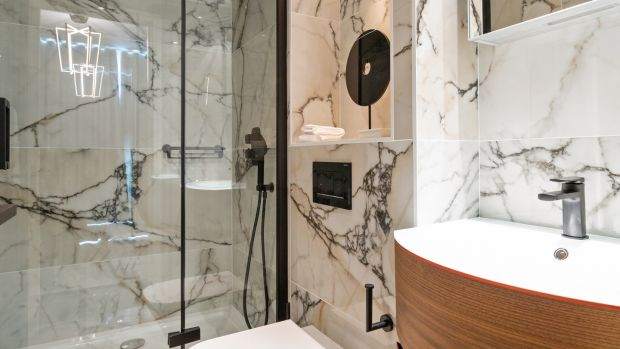 The bath was taken out and a walk-in shower added, with bespoke glass screen. Photograph: Matteo TunizMediaPro