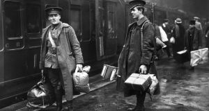December 1914: Two soldiers on the concourse at Victoria station, London, about to leave for the front line. They are carrying parcels full of food and other provisions. (Photo by Topical Press Agency/Getty Images)
