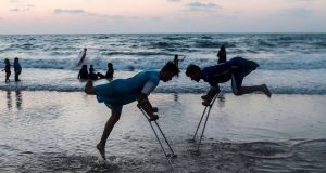 Palestinian amputees Mohammed Eliwa (17)  and Ahmed al-Khoudari (20), who lost their legs during clashes on the border with Israel, on the beach in Gaza City. Photograph: Mahmud Hams/AFP