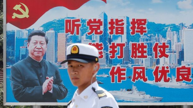 A People's Liberation Army sailor passes by a backdrop featuring Chinese president Xi Jinping at Stonecutters Island naval base in Hong Kong in June. Photograph: Tyrone Siu/Reuters