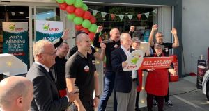 Store owner Ken O'Connor (centre) and the staff at the Texaco Service Station and Spar shop in Enniskerry celebrate selling the winning ticket for the €11.2 million jackpot on Wednesday. Photograph: Tim O'Brien