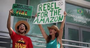 Angel Montalvo and Emily Bench protest for the protection of the Amazon rainforest in front of the Brazilian consulate in Coral Gables, Florida. Photograph: Joe Raedle/Getty