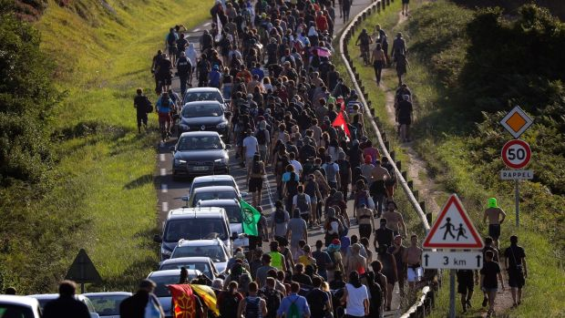 Anti-G-7 activists march along a road near a tent camp near Hendaye, France on Friday. Photograph: Emilio Morenatti/AP