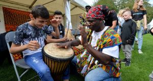 Joshua Torto from Ghana, a member of Afro Irish Drum and Dance, gives a lesson to  David Rafil and Elisei Ciurar from Romania at the Festival of Nations in Mountjoy Square on Saturday. Photograph: Alan Betson/The Irish Times.