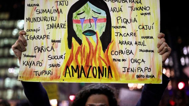 A protester holds a sign with the names of various indigenous tribes during a demonstration to demand for more protection for the Amazon rainforest, in Sao Paulo, on Friday. Photograph: Nacho Doce/Reuters