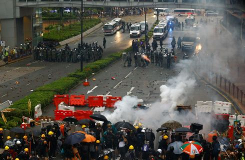 HONG KONG: Riot police shoot tear gas as demonstrators take cover behind barricades during a protest in Tsuen Wan, in Hong Kong. Photograph: Thomas Peter/Reuters