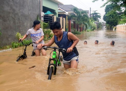 FLOODS: Filipino villagers navigate a flooded road in the town of Bacarra, Ilocos Norte province. According to news reports, two deaths were recorded in the northern Philippine province of Ilocos Norte on August 24th, after heavy rains from tropical storm Bailu hit the area. Photograph: Bernie Sipin Dela Cruz/EPA
